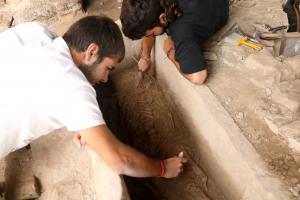 Pla mitjà on es poden veure dos arqueòlegs netejant les restes del cos