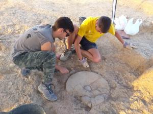 Pla obert on es poden veure dos arqueòlegs al costat de la base del torn de modelatge