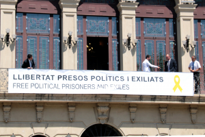 Treballadors municipals penjant la pancarta de suport als presos independentistes