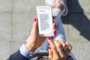 Imatge d'un telèfon mòbil amb un SMS enviat per Aqualia