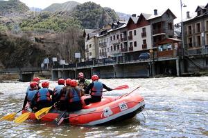 Una barca de ràfting amb el poble de Llavorsí, al Pallars Sobirà, al fons.
