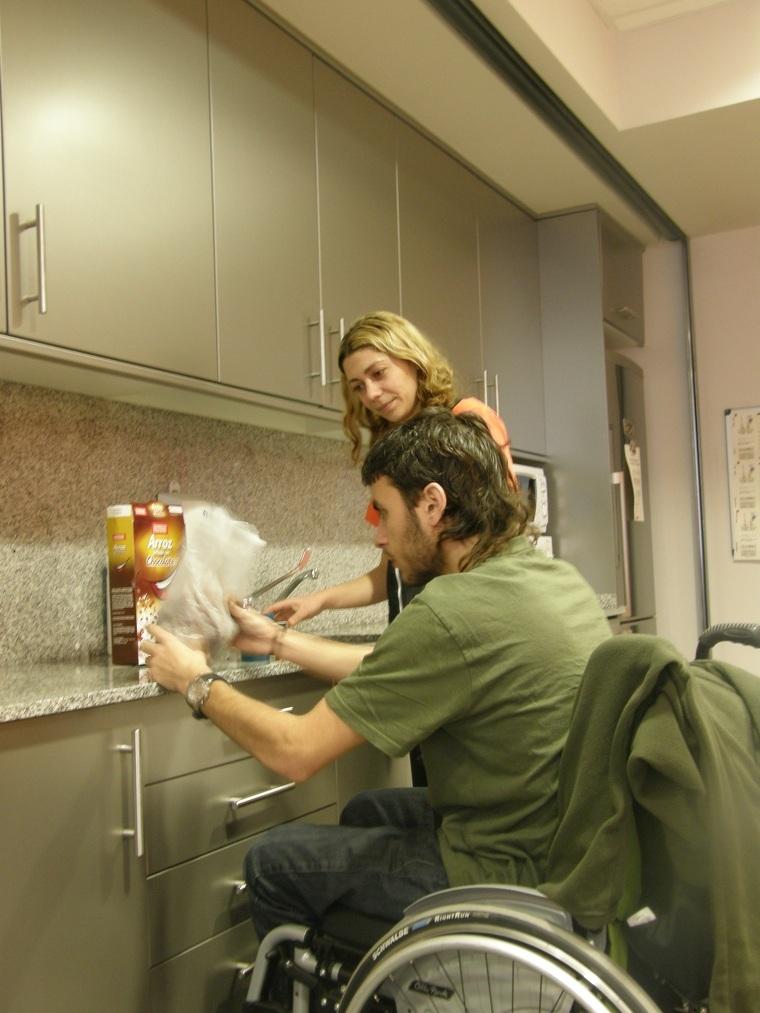 Una assistent ajuda un dels usuaris del Servei d'Atenció Domiciliària d'Aspid