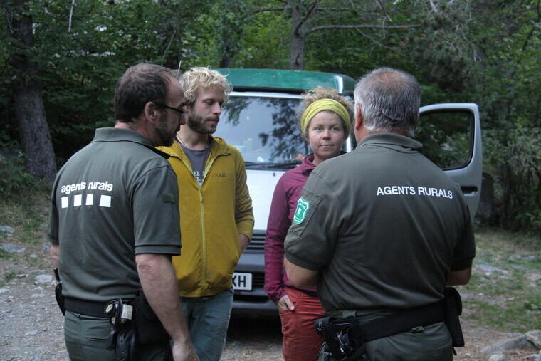 Pla mitjà d'efectius dels Agents Rurals informant a dos visitants del Parc Nacional d'Aigüestortes