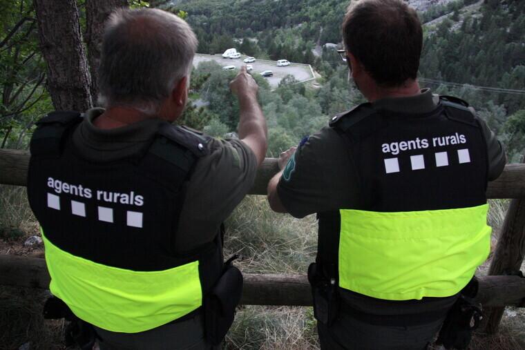 Pla mitjà on es veuen dos efectius dels Agents Rurals observant un dels aparcaments