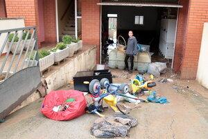 Imatge d'una veïna d'Arbeca inspeccionant els baixos inundats de casa seva