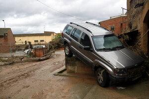 Pla mitjà on es pot veure un cotxe 4x4 arrossegat pel corrent de l'aigua