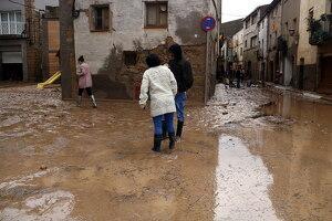 Pla obert on es poden veure veïns de l'Albi caminant entre l'aigua i el fang