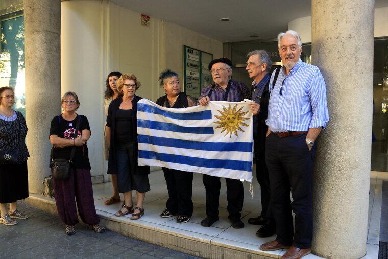 Un grup de persones despleguen una bandera de l'Uruguai davant del consolat a Barcelona