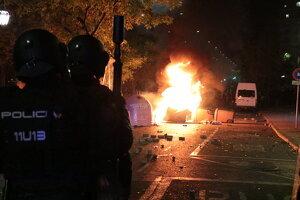 Antiavalots de la policia espanyola observant contenidors encesos i els manifestants