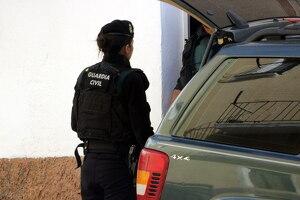 Pla curt on es pot veure una agent de la Guàrdia Civil a l'entrada d'un domicili