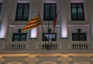 Uns encaputxats despenjant la bandera espanyola de la façana de la Paeria de Lleida