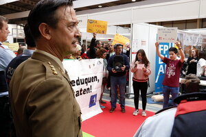 Membres de la plataforma 'Desmilitaritzem l'Educació', amb pancartes, a la Fira d'FP de Lleida