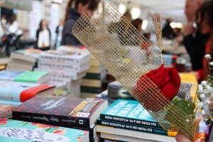 Una parada de llibres de Sant Jordi amb una rosa en primer pla