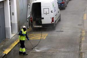 Pla mitjà on es poden veure serveis de neteja desinfectant un carrer de Mollerussa