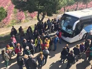Pla obert on es poden veure persones al costat d'un autocar