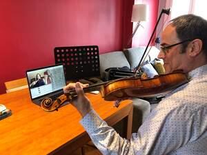 Un professor de L'Intèrpret impartint una classe de violí a una alumna a través de videoconferència