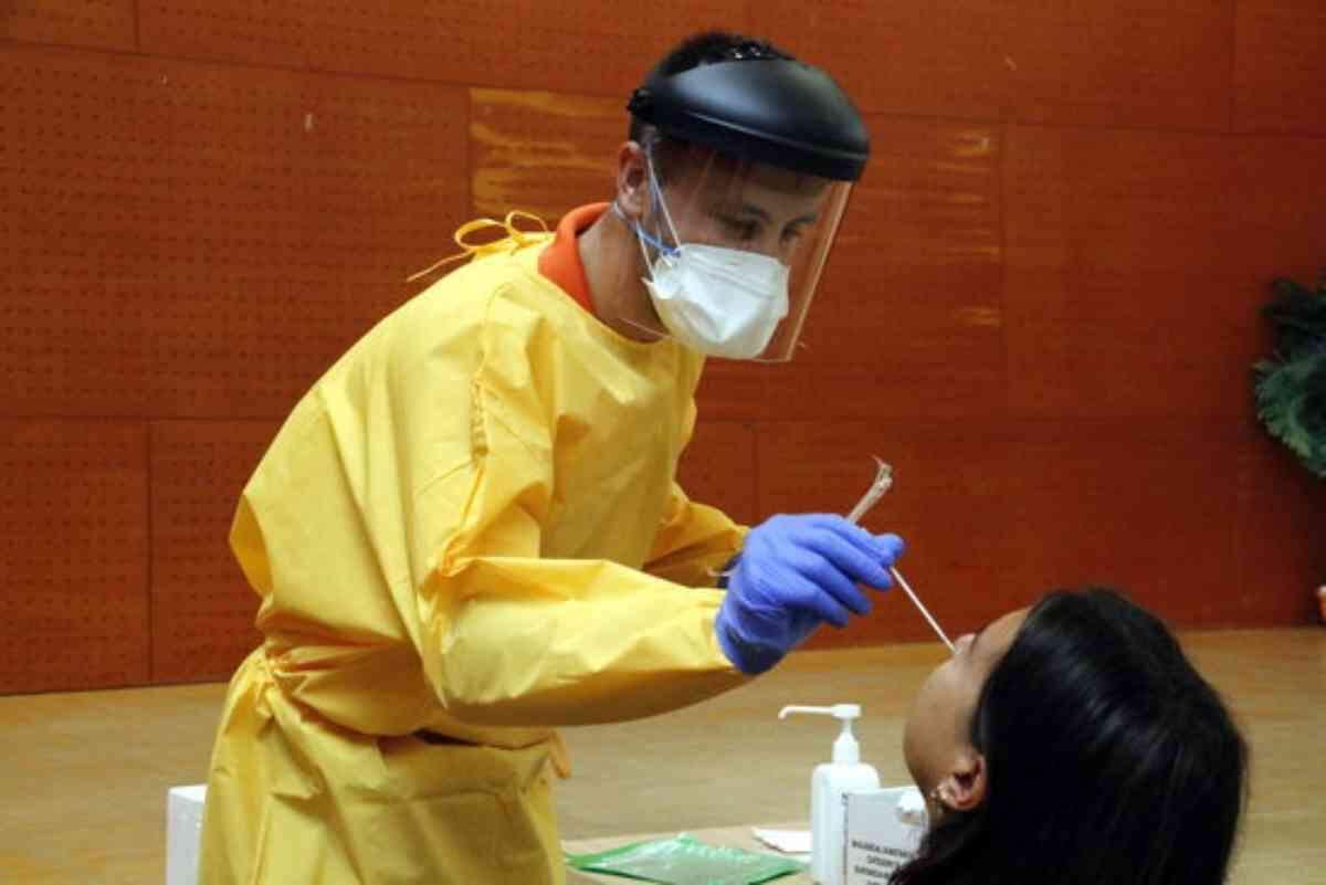 Pla mitjà on es pot veure un sanitari fent una prova PCR a un veí del barri de Balàfia de Lleida en el marc del cribratge massiu