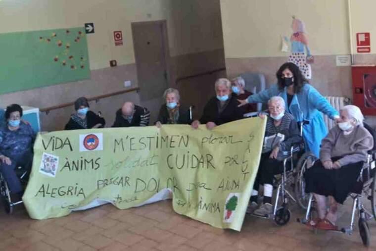 Pla general d'usuaris de la residència de Solsona amb una pancarta feta durant les sessions de treball del dol