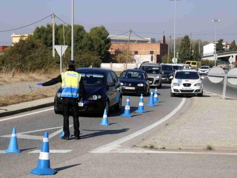 Pla obert d'un agent de la Guàrdia Urbana aturant un vehicle al control que han muntat a la N-230 direcció Lleida