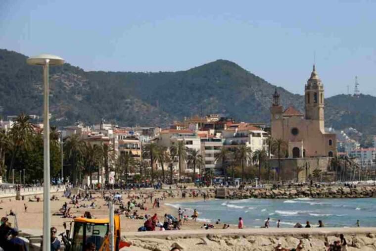 Gran pla general de la platja de Sitges amb nombroses persones prenent el sol