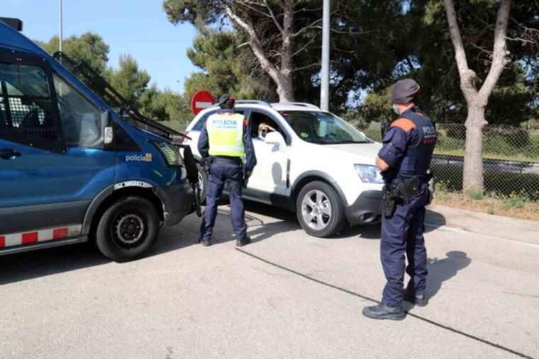 Pla general de dos agents dels Mossos duent a terme un control de mobilitat a l'àrea de servei del Baix Ebre, a l'AP-7
