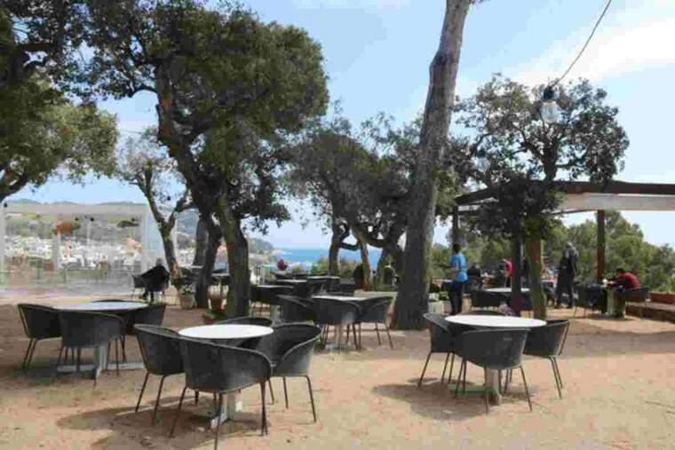 Pla general d'una terrassa d'un bar de Calella de Palafrugell pràcticament buida