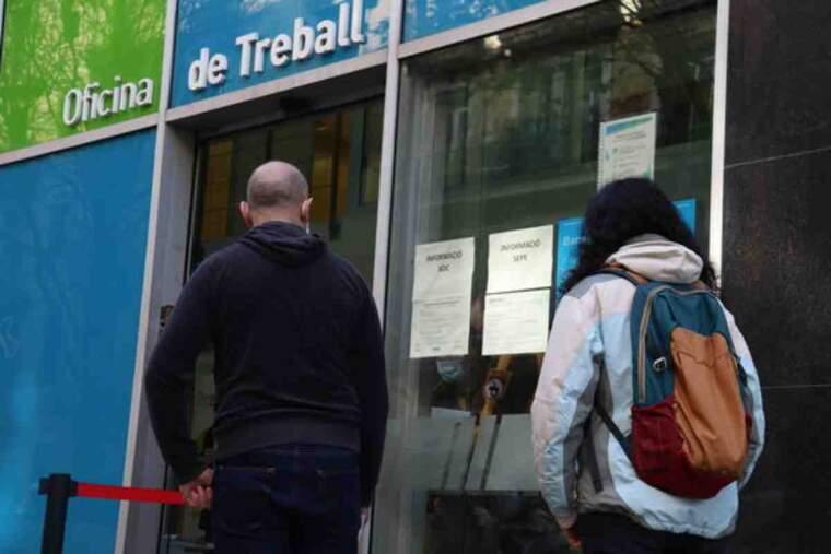 Pla mijtà de dues persones esperant per entrar a l'Oficina de Treball del carrer Sepúlveda de Barcelona en el primer dia de vaga al SEPE