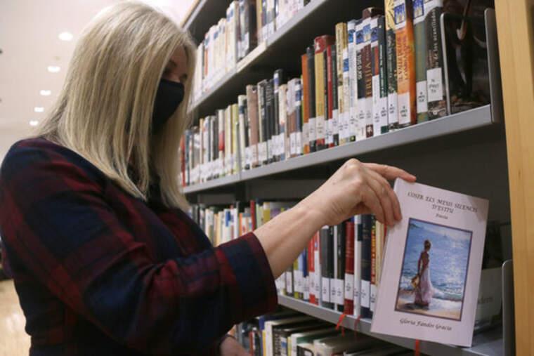 Pla mitjà de la directora de la biblioteca Marcel·lí Domingo de Tortosa, Irene Prades, deixant a la prestatgeria el llibre de poesia 'Cosir els meus silencis d'estiu'
