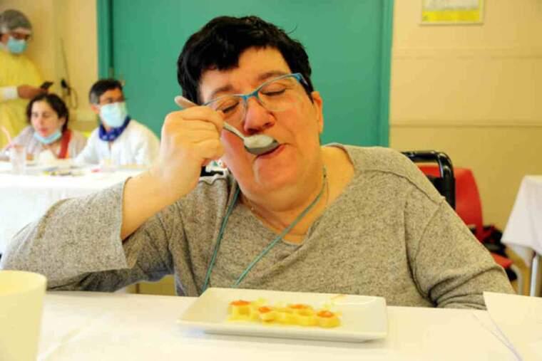 Pla mitjà de la Judit, una de les usuàries del centre de disminuïts físics, tasta un plat de patates braves fet a partir de la tecnologia 3D