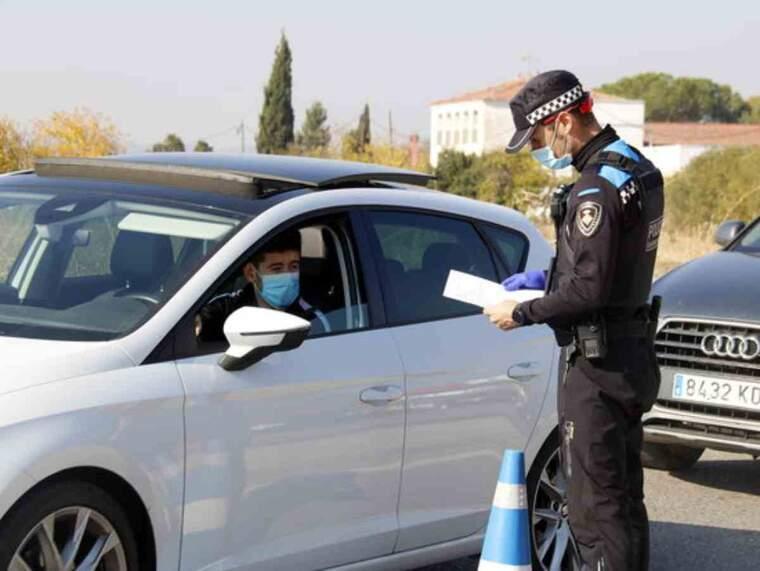 Pla mitjà d'un agent de la Guàrdia Urbana mirant el paper justificant de mobilitat d'un conductor a un control a la N-230 direcció Lleida