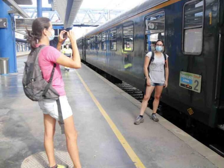 Pla obert d'una noia fent una fotografia a una amiga seva davant el Tren dels Llacs a l'estació de Lleida