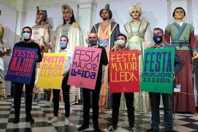 Pla sencer de l'alcalde de Lleida, Miquel Pueyo, amb el regidor de Festes, Ignasi Amor, entre altres, mostrant els cartells del programa de la Festa Major de Maig 2021