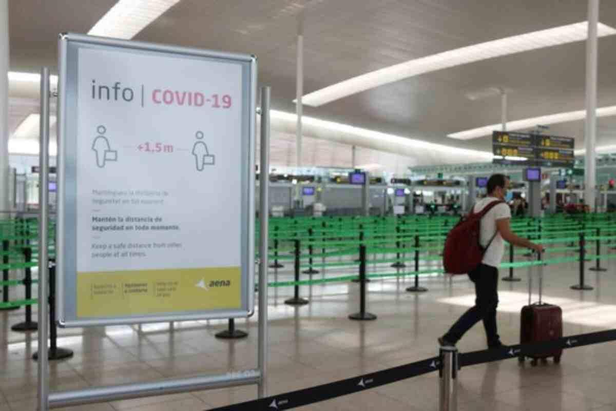Pla general d'un cartell informatiu de la covid-19 i d'un passatger arrossegant una maleta amb el control de seguretat de la T1 de l'Aeroport del Prat