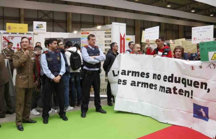 Membres de la plataforma 'Desmilitaritzem l'Educació', amb pancartes, a la Fira d'FP de Lleida, protesten contra la presència de l'Exèrcit