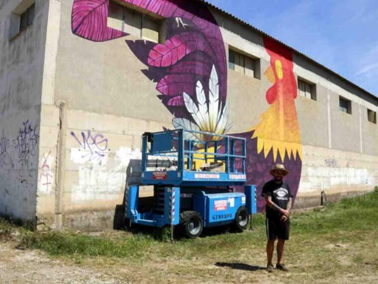 Pla general de l'artista Malpegados davant del mural de grans dimensions que està pintant en la 6a edició del Gargar