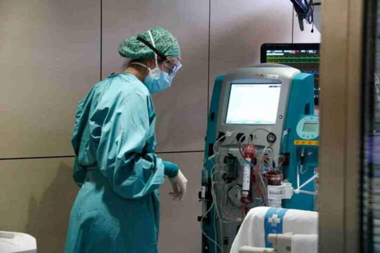 Pla general d'una infermera mirant-se una màquina amb el filtre Seraph 100 després de ser utilitzat per filtrar la sang d'un pacient amb covid-19