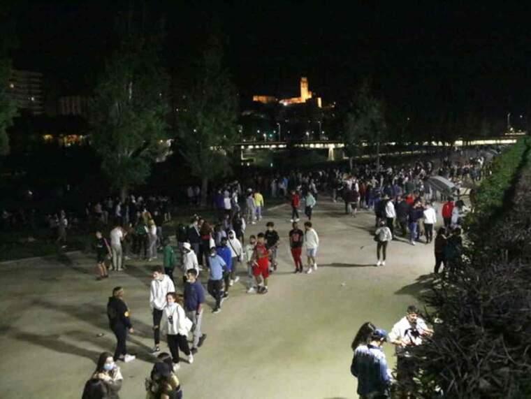 Pla general on es veuen desenes de joves al marge del riu Segre celebrant la fi del toc de queda nocturn