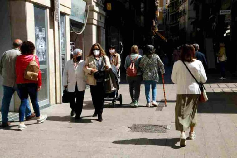 Pla mitjà on es pot veure l'Eix Comercial de Lleida amb gent caminant amb mascareta