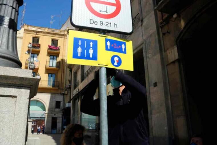 Pla mitjà on es pot veure un operari col·locant un cartell on es recorden les mesures anti covid-19 en un dels accessos a l'Eix Comercial de Lleida