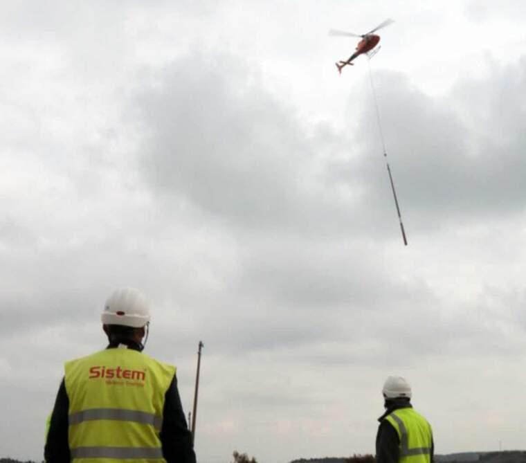 Pla obert dels operaris esperant per rebre el suport per a la línia elèctrica que transporta l'helicòpter
