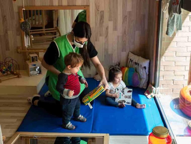Pla obert d'una professora amb dos nadons, a l'Escola Bressol de Balàfia de Lleida