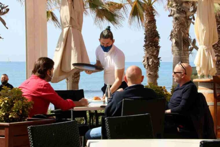 Pla tancat d'un cambrer servint una taula en una terrassa de Sitges