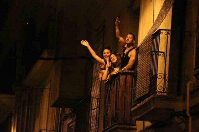 Tres joves des d'un balcó del barri de Gràcia celebren que acaba el toc de queda nocturn