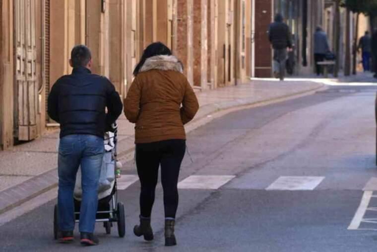 Una parella amb un cotxet passejant pel nucli urbà de l'Espluga de Francolí (Conca de Barberà) i altres vianants, al fons, tots d'esquenes