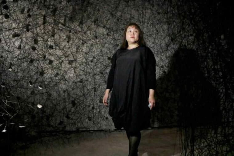 Pla mitjà on es pot veure l'artista japonesa, Chiharu Shiota, observant l'obra 'In the beginning was...'