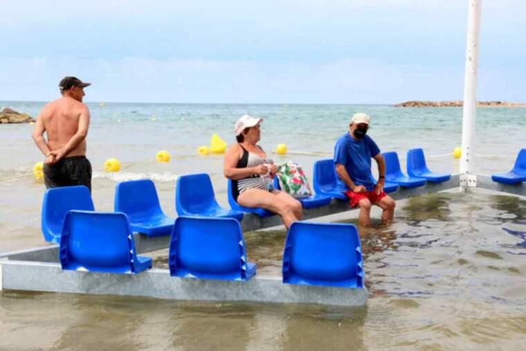 Pla obert de tres banyistes utilitzant la nova àrea accessible per a persones amb mobilitat reduïda a la platja de Cunit