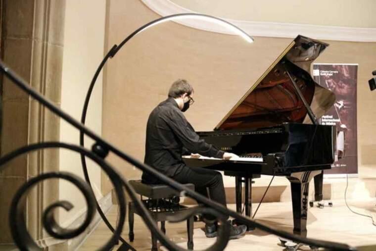 Pla obert d'un alumne tocant el piano en la presentació de la 40a edició de la Càtedra Emili Pujol de Cervera