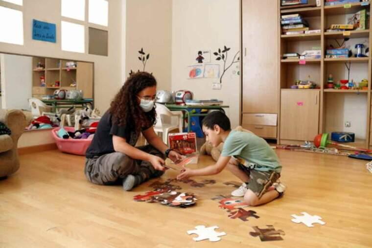 Pla obert d'una animadora voluntària jugant amb un nen a fer un puzzle a l'Escola Popular Balàfia