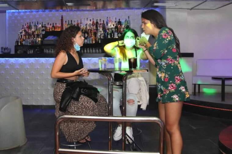 Pla sencer de tres clientes de la discoteca Totem, fent una copa en una de les taules que s'han col·locat