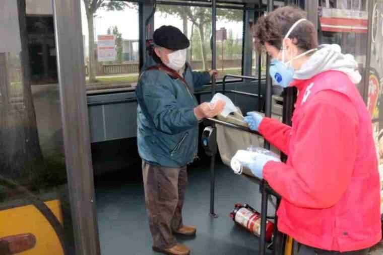 Un voluntari de Creu Roja lliurant una mascareta a un usuari d'un autobús a Lleida